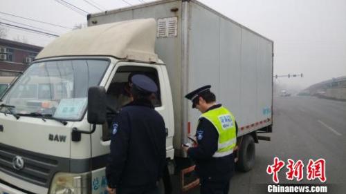 12月8日下午,京开高速路辅路大庄桥路段,环境监察人员检查路上行驶的大货车。 张尼 摄